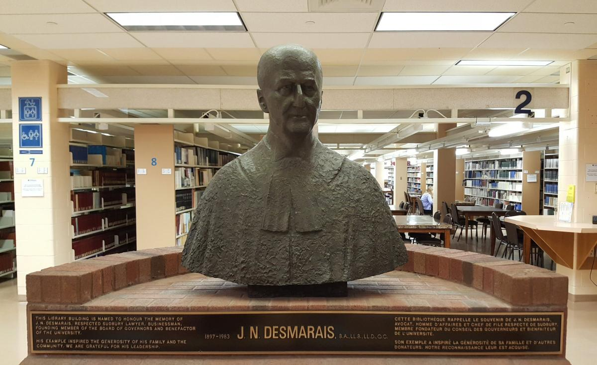 bust of Jean Nöel Desmarais, in front of library shelves
